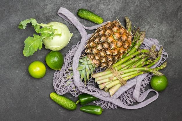 Grüner spargel und ananas im netzbeutel aus stoff. kohlrabi-kohl, limette und gurken auf dem tisch. schwarzer hintergrund. flach legen