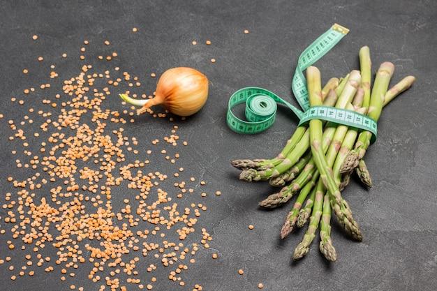 Grüner spargel wird mit maßband im bündel gebunden. zwiebel und linsen auf dem tisch. schwarzer hintergrund. ansicht von oben.