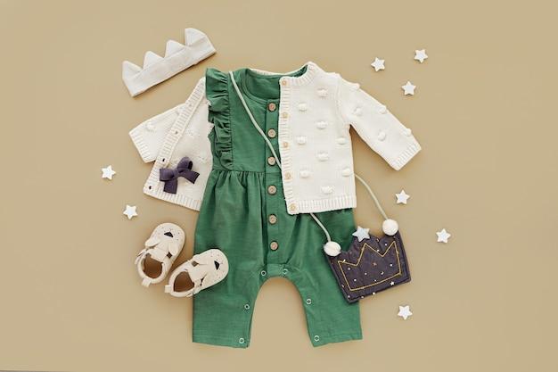 Grüner strampler mit strickpullover, kinderhandtasche, baumwollkrone und babystiefeln. set von babykleidung und accessoires. mode kinder outfit. flache lage, ansicht von oben