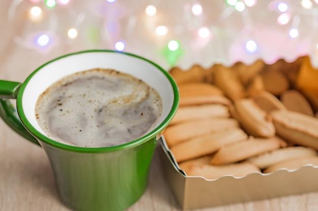 Grüner tasse kaffee und kasten ingwerplätzchen auf holztisch.