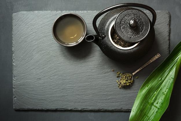 Grüner tee auf schwarzem schiefer.