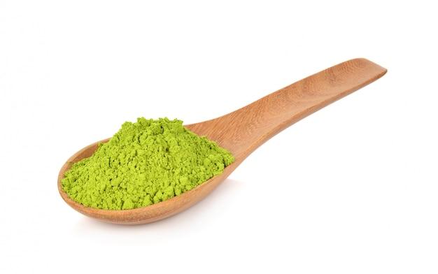 Grüner tee des pulvers auf dem hölzernen löffel lokalisiert auf weiß
