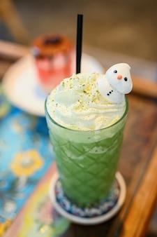 Grüner tee frappe und gemischt. sweety smoothie-getränk zum entspannen und gesundwerden an heißen sommertagen.