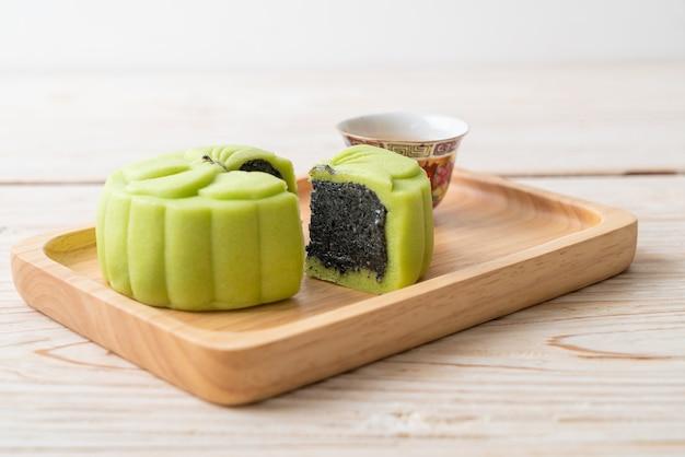 Grüner tee geschmack des chinesischen mondkuchens mit tee auf holzteller