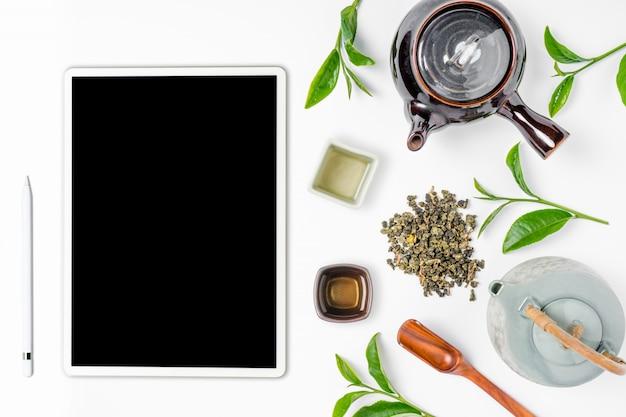 Grüner tee im teetopf auf weißem hintergrund. draufsicht