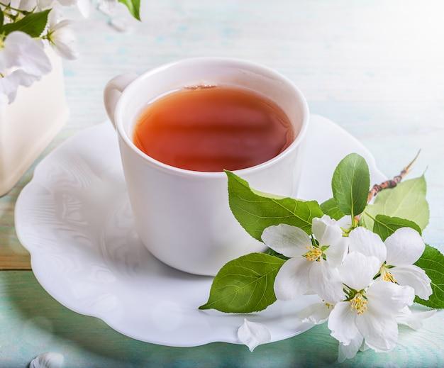 Grüner tee in der weißen tasse mit zweig des blühenden apfelbaums auf geformter untertasse auf holztisch. nahansicht.