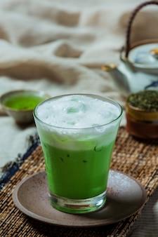 Grüner tee in einem hohen glas mit sahne und grünem eistee. mit grünem teepulver dekoriert.