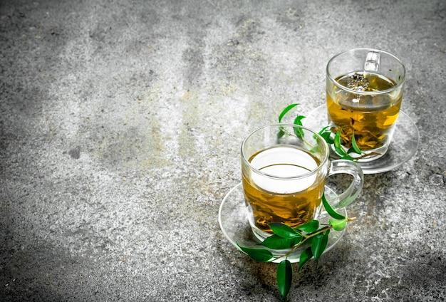 Grüner tee in einer glasschale auf rustikalem tisch.