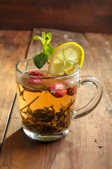 Grüner tee in einer glasschale mit erdbeerminze und zitrone auf einem vertikalen foto des holztischs