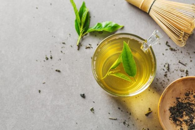 Grüner tee in tasse mit teeblättern auf tisch gebraut. nahansicht.