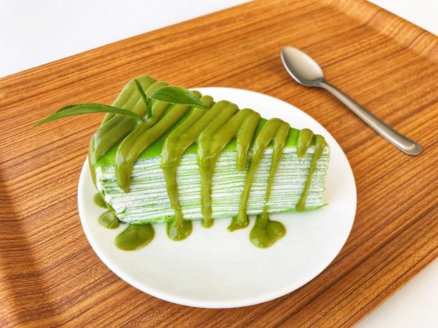 Grüner tee-kreppkuchen mit frischem grünem teeblatt auf weißer keramischer platte und löffel setzten an umwerben