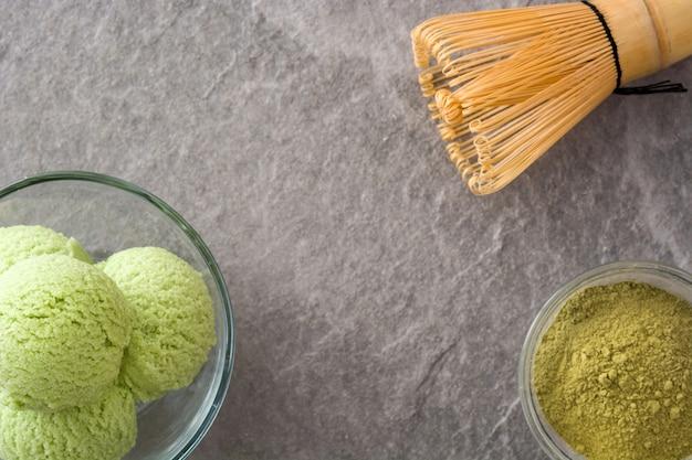 Grüner tee matcha eisportionierer in kristallschale auf grauem stein