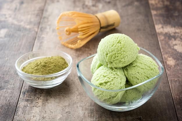 Grüner tee matcha eisportionierer in kristallschale auf holztisch