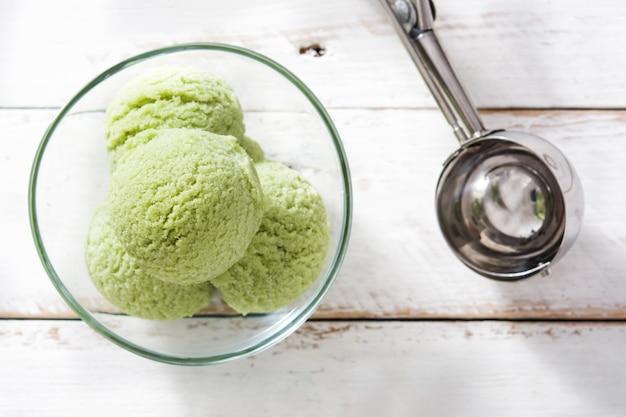 Grüner tee matcha eisportionierer in kristallschale auf weißem holztisch