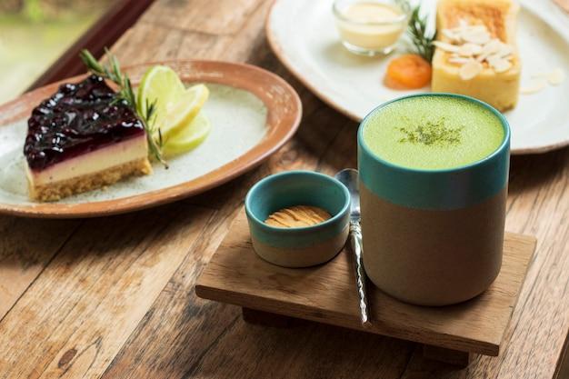 Grüner tee matcha in einem schalen- und nachtischkuchen auf tabelle