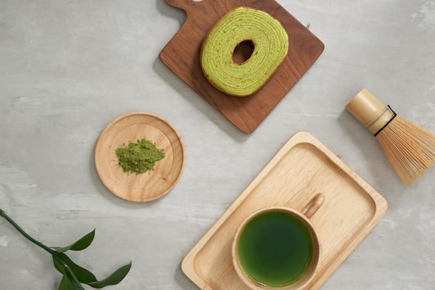 Grüner tee matcha in einer holztasse mit deutschem kuchen auf der braunen matte nahaufnahme