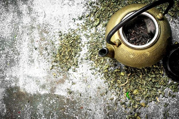 Grüner tee mit einer teekanne. auf einem rustikalen hintergrund.