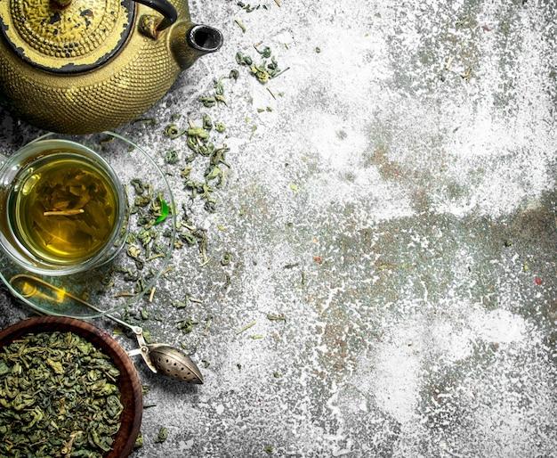 Grüner tee mit einer teekanne auf rustikalem tisch.