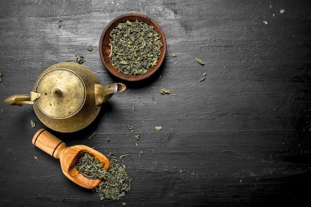 Grüner tee mit einer teekanne auf schwarzer tafel
