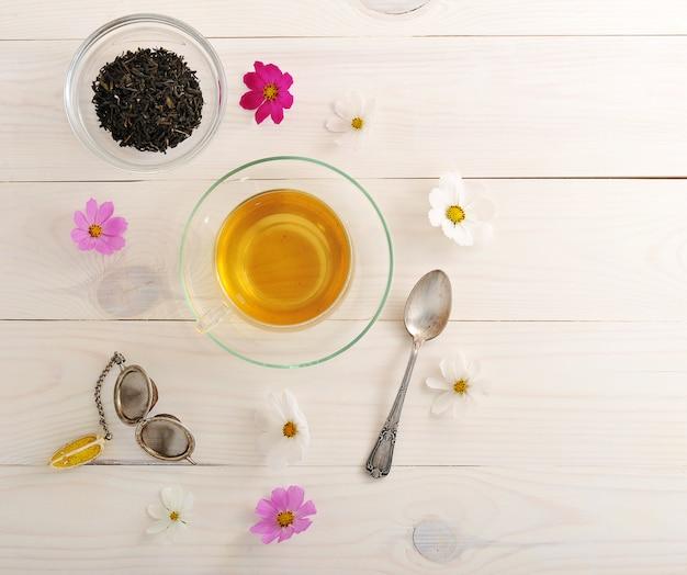 Grüner tee mit gänseblümchen in einem klarglasbecher und in einem teesieb