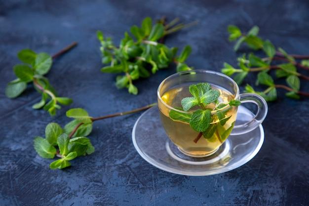 Grüner tee mit minze auf einem dunklen tisch.