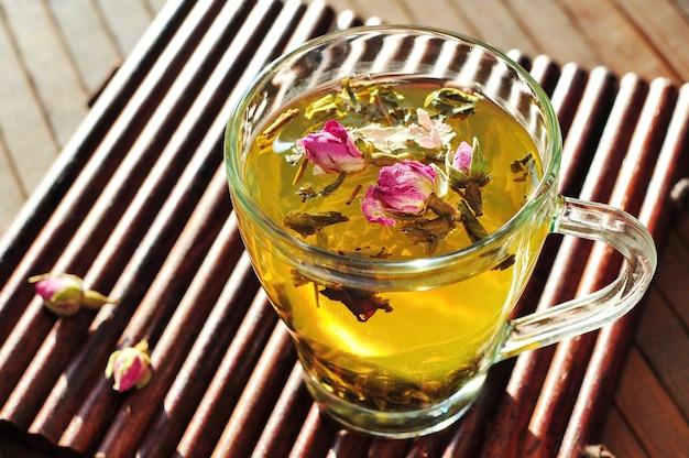 Grüner tee mit trockenen rosen in der glasschale