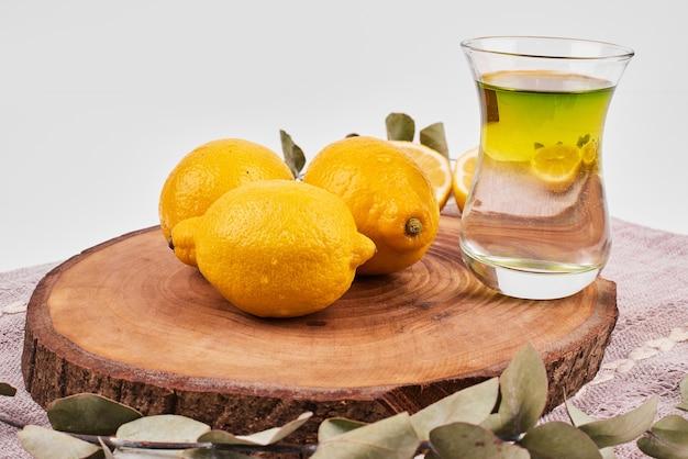 Grüner tee mit zitronen auf rundem holzbrett.