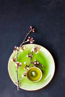 Grüner tee und pfirsichblüte als frühling