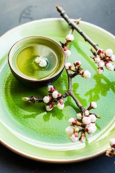 Grüner tee und pfirsichblüte als frühlingskonzept im asiatischen stil