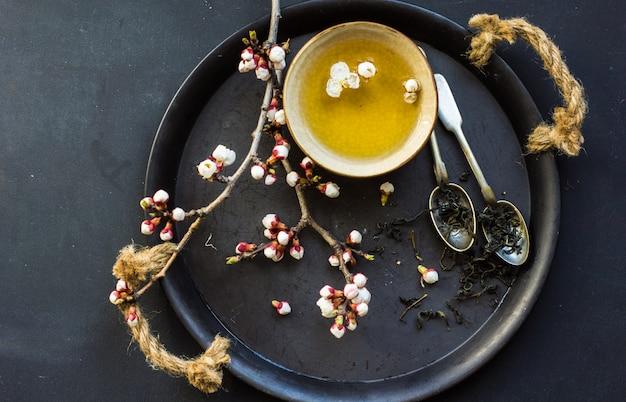 Grüner tee und pfirsichblüte als frühlingskonzept