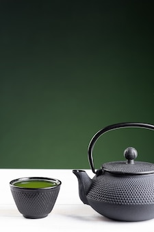 Grüner tee und teekanne auf grünem hintergrund auf weißem holzsockel mit exemplar. traditionelles japanisches getränk. vertikales format.