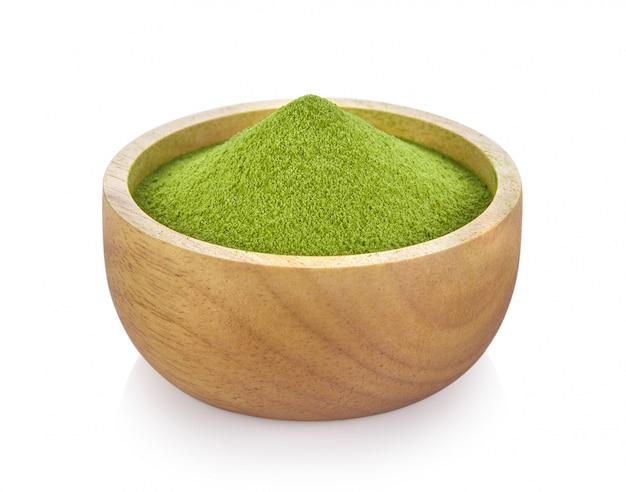 Grüner teepulver in der holzschale auf weißem raum