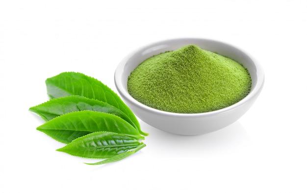 Grüner teepulver in einer schüssel und blatt auf weiß