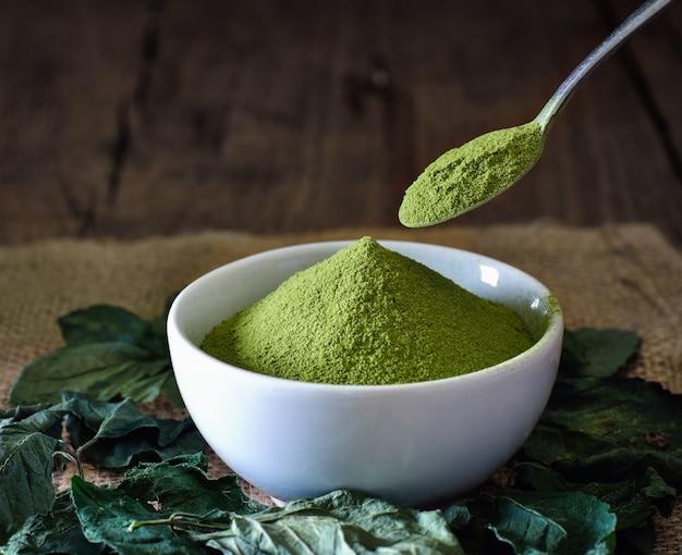 Grüner teepulver in weißer schüssel