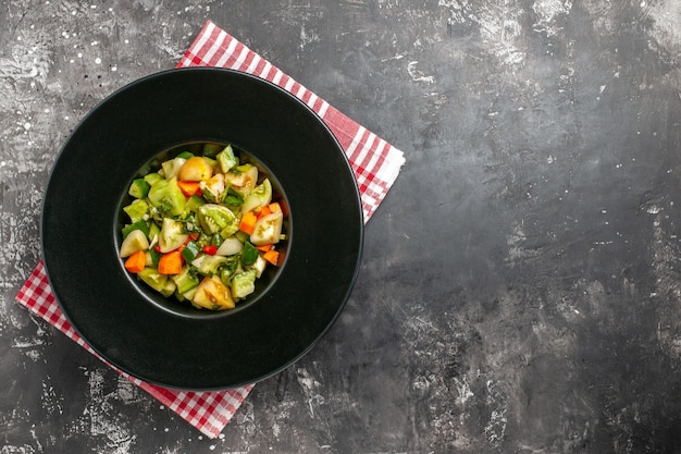 Grüner tomatensalat der draufsicht auf ovalem teller auf dunklem hintergrund