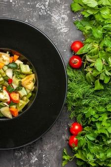 Grüner tomatensalat von oben in der nähe auf ovaler platte grünt tomaten auf dunklem hintergrund