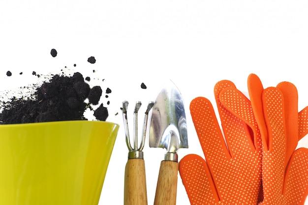 Grüner topf mit verschüttetem boden, orangefarbenen handschuhen, einer kleinen schaufel und einem rechen