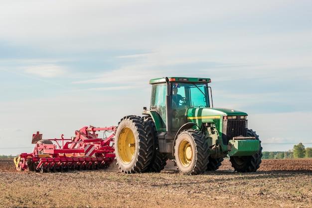 Grüner traktor mit einem pflug in einem feld in den strahlen der nachmittagssonne