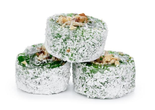 Grüner türkischer genuss mit nüssen auf puderzucker lokalisiert auf weiß