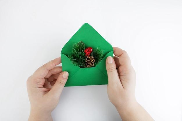 Grüner umschlag mit einem weihnachtszweig in den weiblichen händen auf einem weißen hintergrund