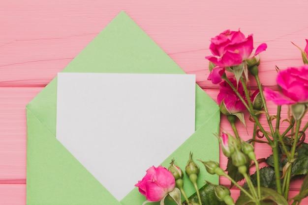 Grüner umschlag mit leeren notiz und rosen