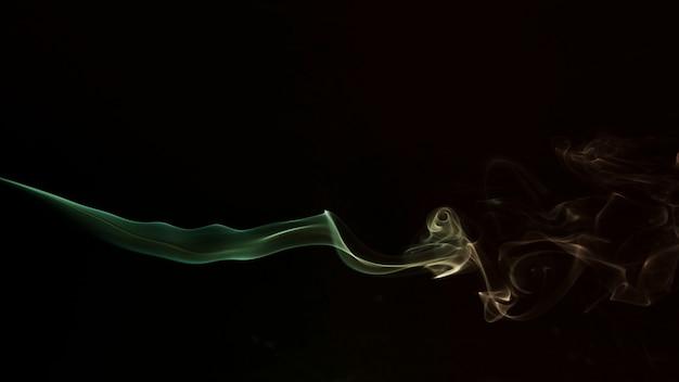 Grüner und gelber wirbelnder rauch auf schwarzem hintergrund