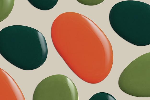 Grüner und orangefarbener farbtropfen in grünem hintergrund