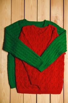 Grüner und roter strickpullover auf einem hölzernen hintergrund. draufsicht. valentinstag konzept