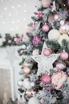 Grüner und weißer weihnachtsbaum mit rosa spielzeug-neujahrs-wintergeschenkdekor