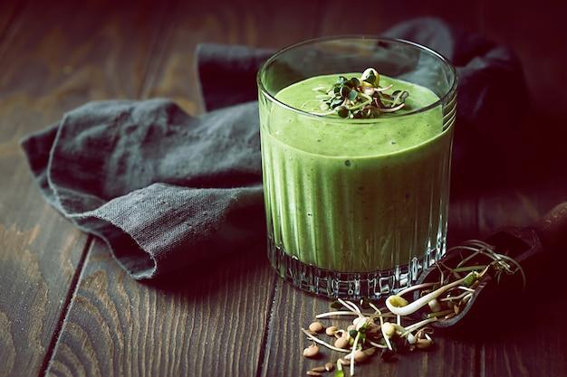 Grüner veganer smoothie mit spinatbanane und gekeimten samen auf dunklem hölzernem hintergrund