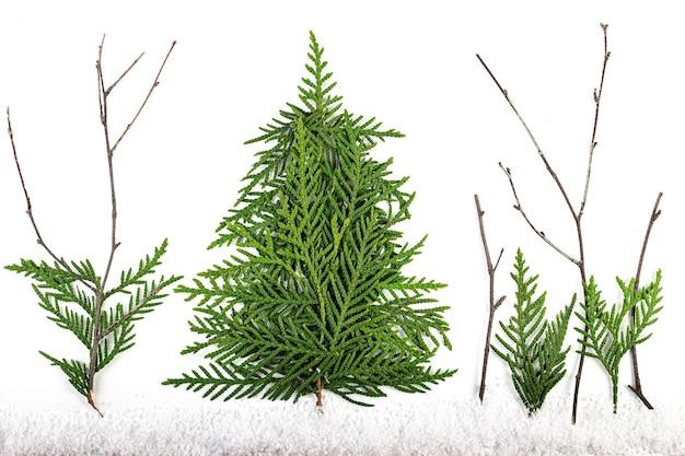 Grüner weihnachtsbaum aus nadelbaumzweigen auf weißer oberfläche