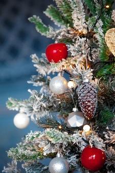 Grüner weihnachtsbaum verziert mit blauen spielzeugen und bällen. weihnachten