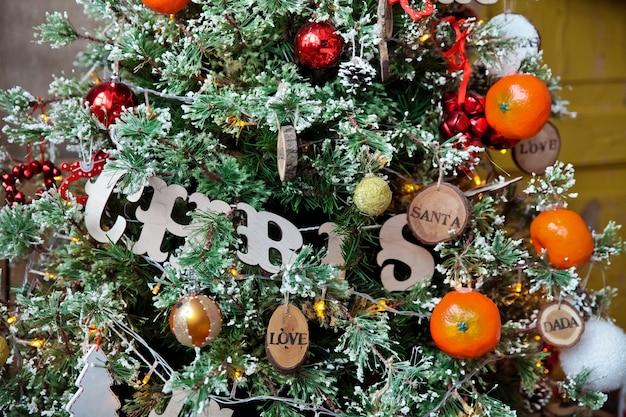 Grüner weihnachtsbaum verziert mit spielzeug und bällen. weihnachtsgrund mit holzschild