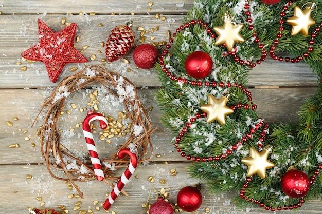 Grüner weihnachtskranz mit dekorationen auf holzuntergrund